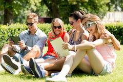 Smiling friends with tablet pc computers in park. Friendship, leisure, summer, technology and people concept - group of smiling friends with tablet pc computers stock images