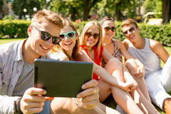 Smiling friends with tablet pc making selfie Royalty Free Stock Photos