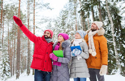 Smiling friends with tablet pc in winter forest Stock Image