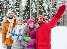 Smiling friends with tablet pc in winter forest Royalty Free Stock Images