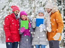 Smiling friends with tablet pc in winter forest Stock Photos