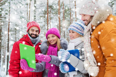 Smiling friends with tablet pc in winter forest Stock Photography