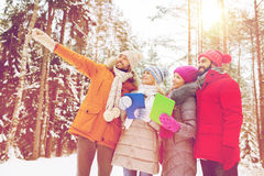 Smiling friends with tablet pc in winter forest Stock Photo