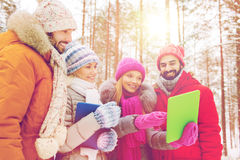 Smiling friends with tablet pc in winter forest Royalty Free Stock Photos