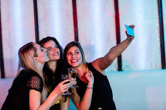 Smiling friends taking a selfie from mobile phone while having wine Stock Photo