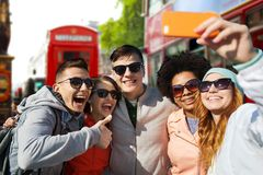 Smiling friends taking selfie with smartphone Stock Photos