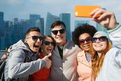 Smiling friends taking selfie with smartphone Royalty Free Stock Photos