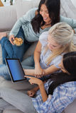 Smiling friends using digital tablet together and eating cookies Stock Photos