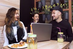 Smiling friends using laptop. Happy young friends  using a laptop, drinking coffee and smiling while sitting at the cafe Royalty Free Stock Photos