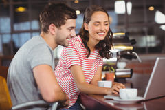 Smiling friends using laptop and having coffee together Royalty Free Stock Photo