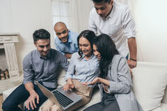 Smiling friends using laptop while sitting on sofa at home Stock Photography