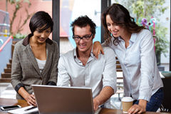 Smiling friends using laptop together. Smiling friends using laptop in a cafe Stock Image