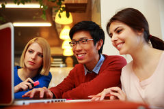 Smiling friends using laptop. Young smiling friends using laptop Royalty Free Stock Image