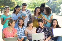 Smiling friends using media devices Stock Photo