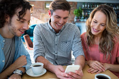 Smiling friends using mobile phone Royalty Free Stock Photo