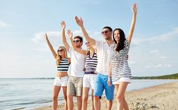 Smiling friends walking on beach and waving hands. Summer, holidays, sea, tourism and people concept - group of smiling friends in sunglasses walking on beach stock image