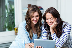 Smiling friends watching video on digital tablet Stock Images