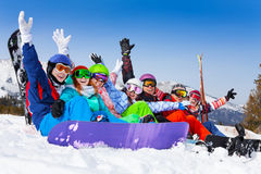 Smiling friends wearing goggles with hands up. Seven happy smiling friends wearing ski mask sitting together lifting hands up in the air on the mountains royalty free stock images