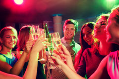 Smiling friends with wine glasses and beer in club Royalty Free Stock Photography