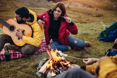 Free Smiling Friends With Marshmallow Sitting Around Bonfire In Camping Royalty Free Stock Photos - 155589518