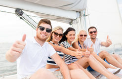 Smiling friends on yacht showing thumbs up Royalty Free Stock Photos