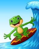 Smiling frog cartoon surfing on big sea waves Stock Image