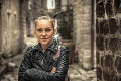 Smiling frozen beautiful woman standing on narrow medieval street  during her travel holidays around Europe in cold overcast rainy Stock Image