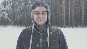Smiling frozen man in the snow looking at the camera in the winter forest after a snow storm immunity and cold. Winter activity Stock Photos