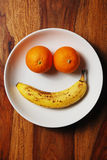 Smiling fruit face. Two oranges and a banana that make up a smiling face on a white plate on a wooden table stock photos