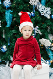 smiling funny Caucasian child girl toddler with blue eyes in red dress and Santa Claus hat sitting on gist box by New Year tree Stock Photo