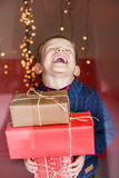 Smiling funny child holding Christmas gift in hand. Christmas concept. Birthday Stock Photos