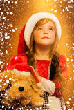 Smiling funny child (kid, girl) in Santa red hat Royalty Free Stock Photography