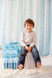 Smiling funny child in Santa red hat holding Christmas gift in h Royalty Free Stock Photos