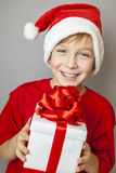 Smiling  funny child in Santa red hat. Holding Christmas gift in hand. Christmas concept Stock Photography