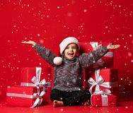 Smiling funny child in Santa red hat holding Christmas gift in hand. Christmas concept. royalty free stock photography