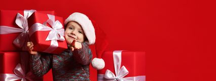 Smiling funny child in Santa red hat holding Christmas gift in hand. Christmas concept. royalty free stock images