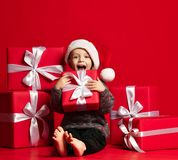Smiling funny child in Santa red hat holding Christmas gift in hand. Christmas concept. stock image