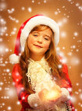 Smiling funny child  in Santa red hat. Smiling funny child (kid, girl) in Santa red hat. Holding Christmas gift in hand. Christmas concept Stock Images