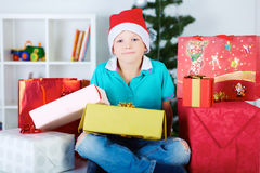 Smiling funny child in Santa red hat with a lot of gift boxes. Stock Image