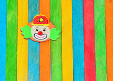 Smiling funny clown face. On the colorful striped background Royalty Free Stock Image