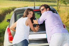 Smiling and funny couple pushing a car Royalty Free Stock Photography