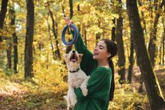 Smiling funny girl playing with pupil. Autumn outdoor portrait of beautiful happy girl walking in park or forest with stock photography