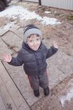 Smiling funny little boy in winter clothes outdoors royalty free stock images