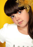 Smiling funny little girl looking at camera isolated on yellow b Stock Photography