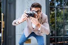 Smiling funny photographer in round glasses taking photos outdoors Stock Photos