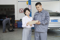 Smiling Garage Mechanic Explaining to Customer, Showing Her the Bill Stock Photo