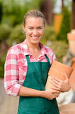 Smiling garden center woman holding clay pots Royalty Free Stock Image