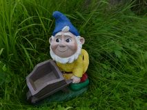 Smiling garden dwarf with a blue hat, yellow jacket and a wheelbarrow  on a green meadow Stock Photo