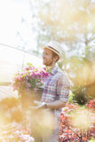 Smiling gardener looking away while holding flower pot outside greenhouse Stock Photos