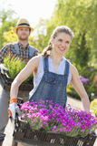Smiling gardeners carrying flower pots in crates at plant nursery Royalty Free Stock Photography